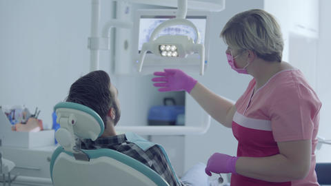 Dentist in medical mask and gloves checking the mouth of the patient using Live Action