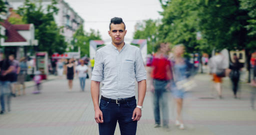 Time lapse of serious mixed race man standing alone in pedestrian street in city Live Action