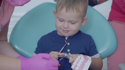 Cute little boy in the dentist office playing with the jaw mock. Carefree child Footage
