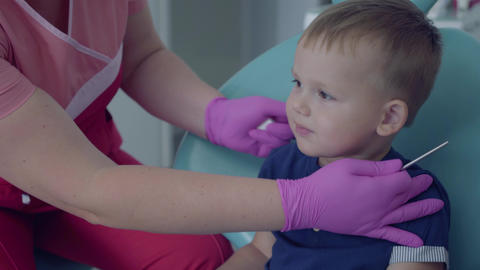 Dentist ready to checking tooths of little carefree boy sitting in the chair in Live Action