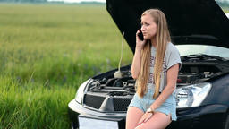 Upset woman talking on phone near broken car Footage