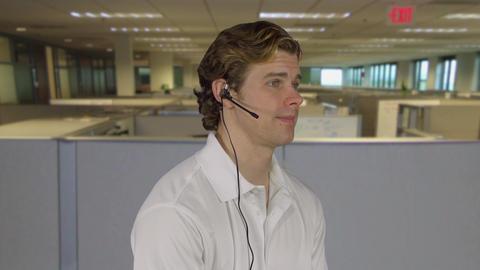 Man handles customer call at work ビデオ