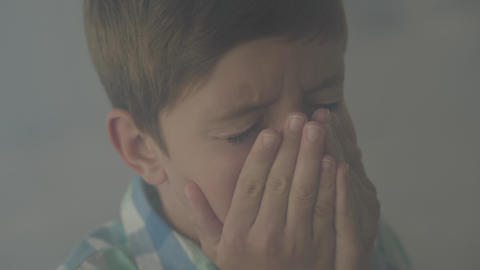Close-up of confused scared boy standing in the smoky room coughing and covering Footage