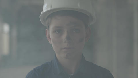 Portrait cute boy in a protective helmet looking at the camera in the background Live Action