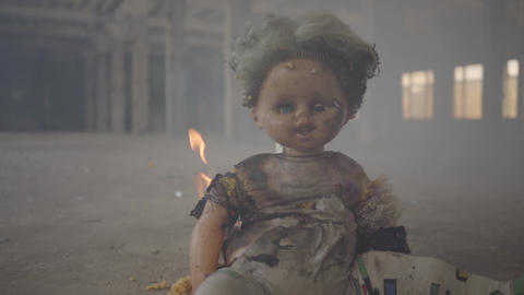 Scary doll burning on the floor in an abandoned smoky building. Concept of fire Live Action