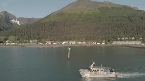 Aluminum fishing boat driving past the Seward Alaska waterfront Live Action