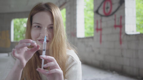Woman shake off heroin from a syringe preparing to make injection close up Footage