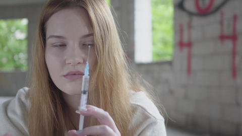 Woman shake off heroin from a syringe preparing to make injection close up Live Action