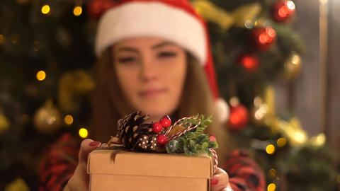 Woman Showing Christmas Gift In Her Hands. Female Hands Live Action