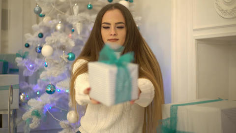 Christmas Scene. Young Woman Giving A Gift Box. Beauty Girl Holding Gift Live Action