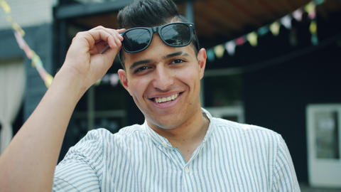 Portrait of cheerful mixed race guy raising sunglasses outside on summer day Live Action