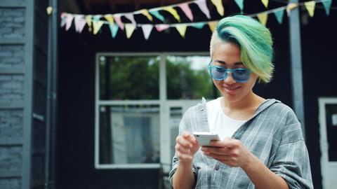 Asian girl using smartphone touching screen outdoors enjoying social media Footage