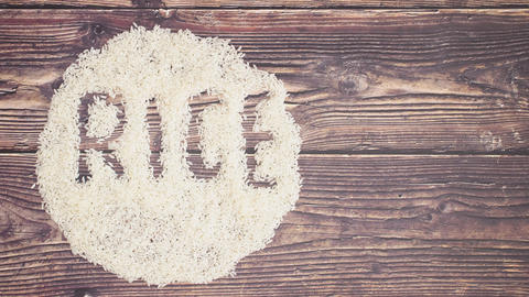 White rice moving on wooden background and write rice - Stop motion Animation