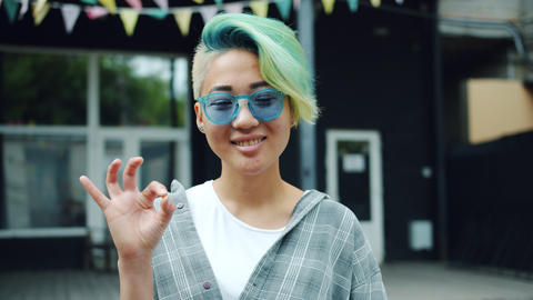 Joyful Asian hipster girl showing OK gesture smiling outside in city street Footage