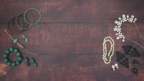 Woman's jewelry appear on wooden background - Stop motion Animation