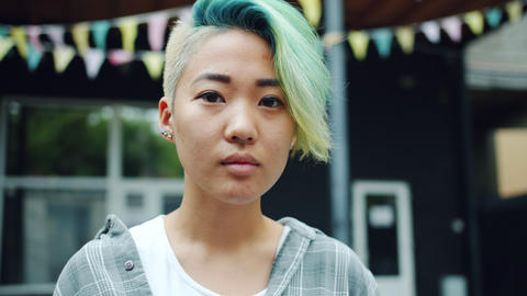 Close-up portrait of cute Asian hipster with dyed hair and nose piercing outside Footage