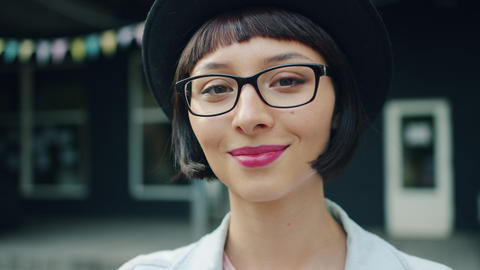 Slow motion headshot of beautiful young woman in hat and glasses outside Footage