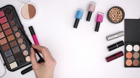 Woman's hand take eye shadow and powder with brush and pick lipstick - Stop motion Animation