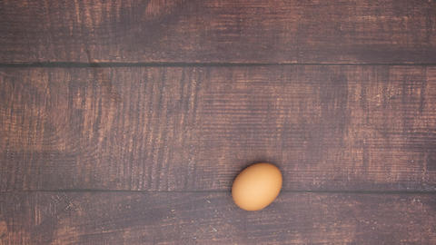 Boiled egg moving on wooden background and peeling off - Stop motion Animation