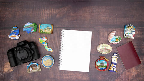 Travel kit, notebook and travel magnets appear on wooden background - Stop motion Animation