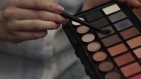 Woman hold a palette of eye shadows and second hand smear the shadows Footage