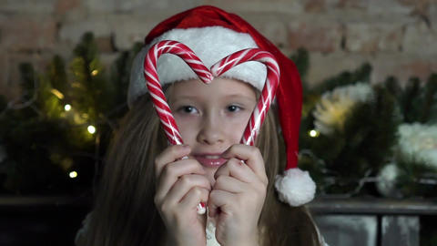 Little Girl Makes A Heart Shape With Candy Canes, She Smiles With Holiday Joy Live Action