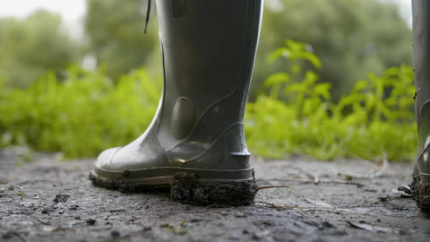 Close up rubber rain boot with mud work on dirty place Live Action
