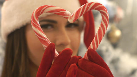 Girl In Santa Hat Holding Christmas Candies In Heart Shape Live Action