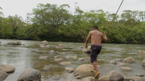 Indigenous Hunter Fishing With A Spear By The River In The Amazon Rainforest Footage