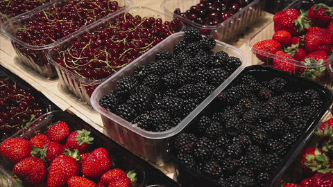 Vegan girl chooses fresh organic blackberries on the store counter in the Footage