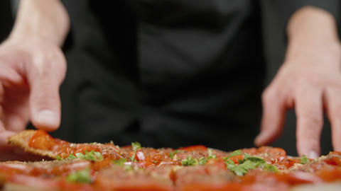 Man tastes vegan pizza in the black kitchen Footage