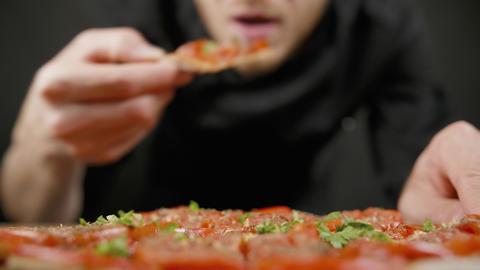 Man tastes vegan pizza in the black kitchen Live Action