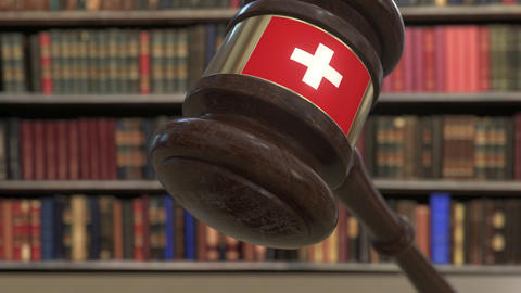 Flag of Switzerland on falling judges gavel in court. National justice or Live Action