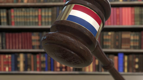 Flag of the Netherlands on falling judges gavel in court. National justice or Live Action
