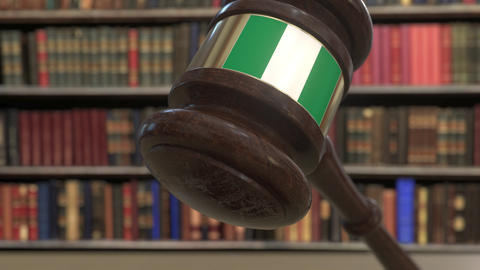 Flag of Nigeria on falling judges gavel in court. National justice or Live Action