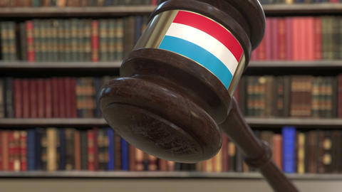 Flag of Luxembourg on falling judges gavel in court. National justice or Live Action