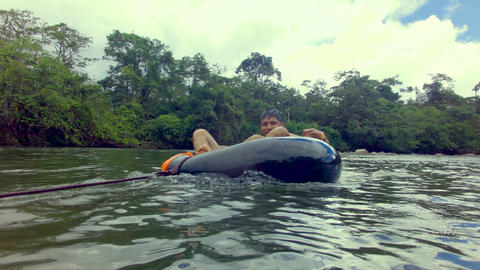 Indigenous Boy Having Fun Over A River Inner Tube On The Amazon Rainforest Footage