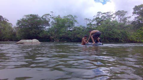 Three Indigenous Children Trying To Stand In A Floating Inner Tube In Ecuador Live Action