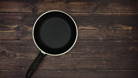 Pan eggs and wooden spoon on wooden background - Stop motion animation Animation