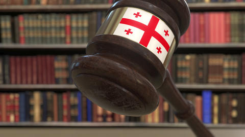 Flag of Georgia on falling judges gavel in court. National justice or Live Action