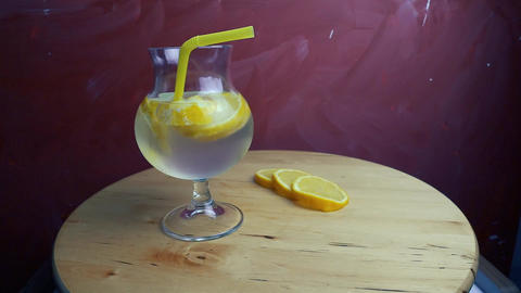 Refreshing soda tonic with lemon and ice in a glass. Cold lemonade mojito drink Footage