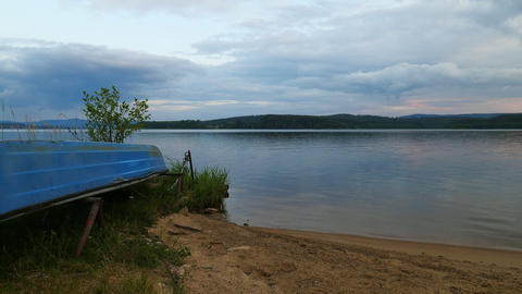 Blue fishing boat anchored on beach sand of lake. Smooth evening water level and calm. Large vallely Footage