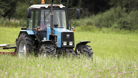 Blue tractor riding on grass field at farm near forest Live Action