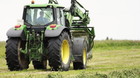 Green tractor riding on grass field at farm holding stack in metal claw Live Action