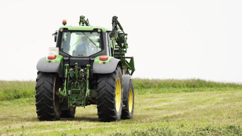 Green tractor riding on grass field at farm holding stack in metal arm Live Action