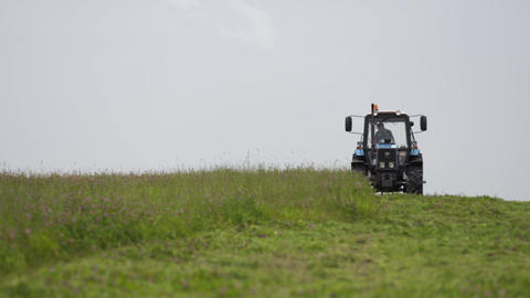 Blue tractor riding on grass margin at farm under gray sky Live Action