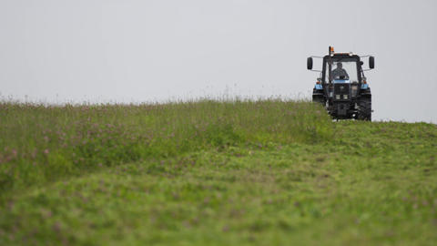 Blue tractor riding on grass field at farm under gray sky Live Action
