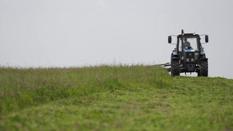 Blue agrimotor riding on grass field at farm under gray sky Live Action
