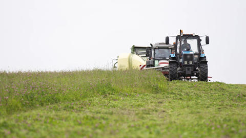 Line of agriculture machines standing on grass field at farm Live Action