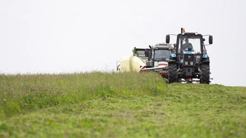 Line of agriculture machines driving on grass field at farm Live Action